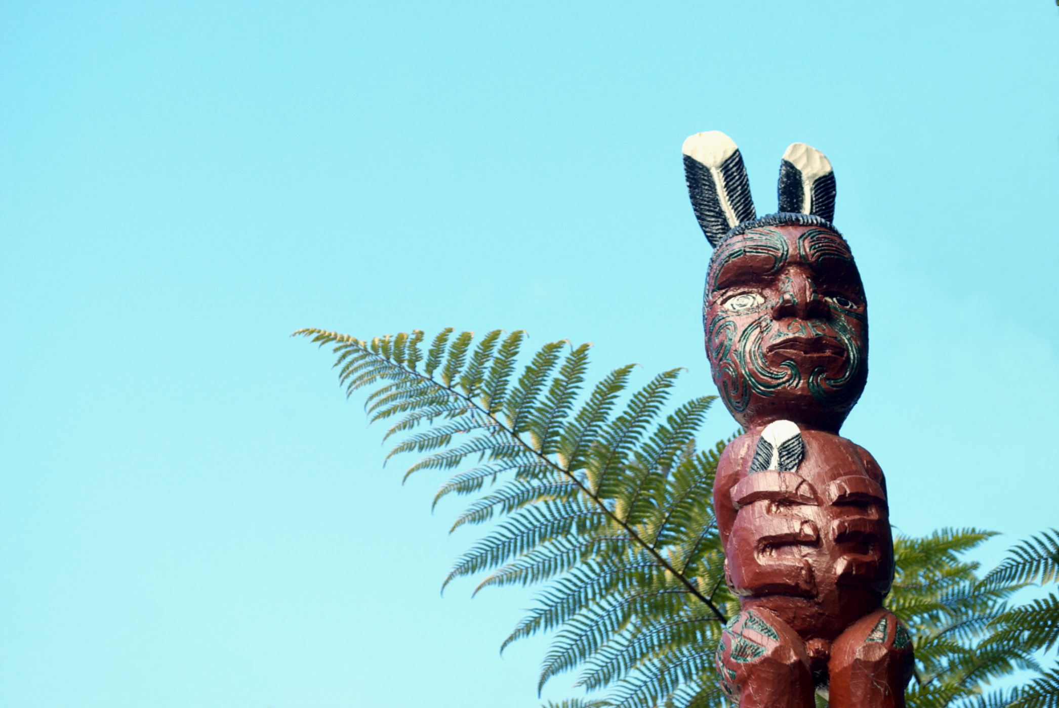 Looking up at a Maori Pou Figure on a Gateway Entarance to Meeting House. In the background a Ponga Fern and clear blue sky for copy space.